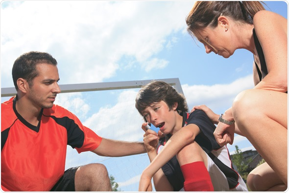 Child playing sport having an asthma attack