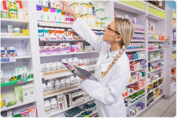 Pharmacist taking medicine from shelf in the pharmacy - Image Copyright: wavebreakmedia / Shutterstock