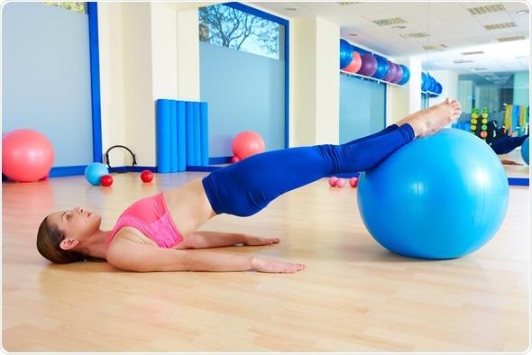 Ejercicio pélvico del fitball de la ascensional de la mujer de Pilates - derechos de autor de la imagen: holbox/Shutterstock
