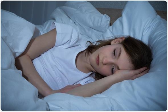 Muchacha en el dormitorio que tiene noche del insomnio - derechos de autor de la imagen: Andrey_Popov/Shutterstock