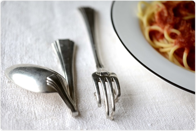 Cranked spoon and fork with a spaghetti dish.