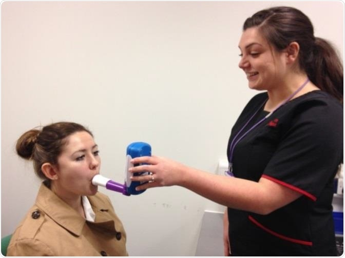 A respiratory physiologist demonstrating the NObreath® FeNO monitor with a student.