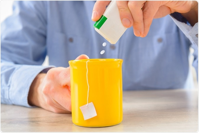 Sweetener tablets and hand with box whit cup of tea. Image Credit: Monika Wisniewska / Shutterstock
