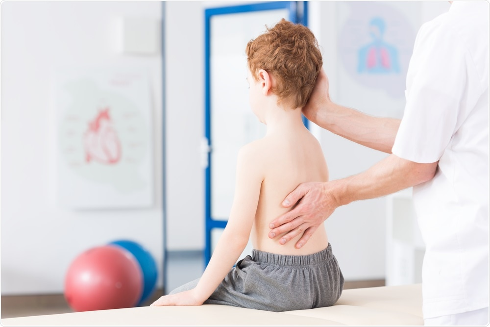 Picture of child with scoliosis being checked over by doctor - Photographee.eu