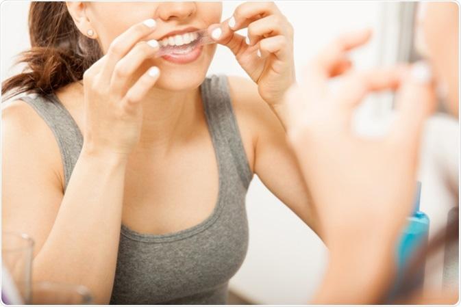 Woman applying a whitening strip on her teeth. Image Credit: antoniodiaz / Shutterstock
