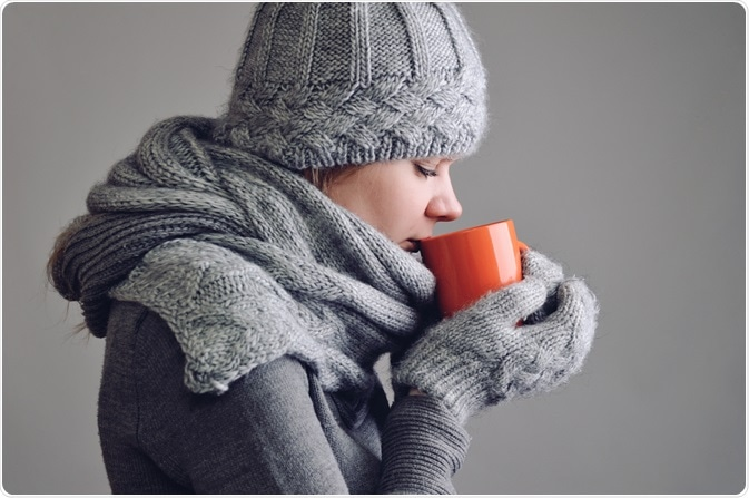 Woman drinking hot drink to prevent hypothermia/keep her core body temperature high - By morozv