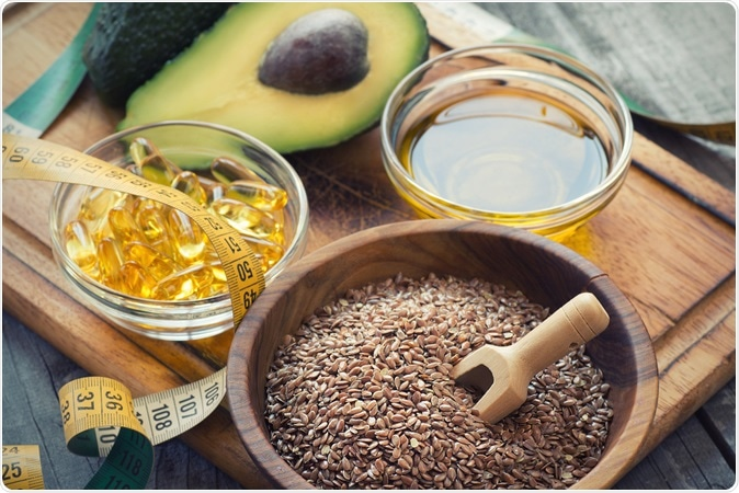 Sources of omega 3 fatty acids: flaxseeds, avocado, oil capsules and flaxseed oil. Image Credit: Lecic / Shutterstock