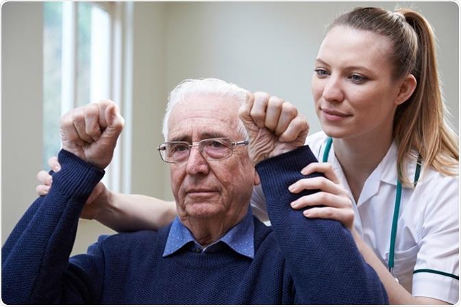 Nurse Assessing Stroke Victim By Raising Arms. Image Credit: SpeedKingz / Shutterstock