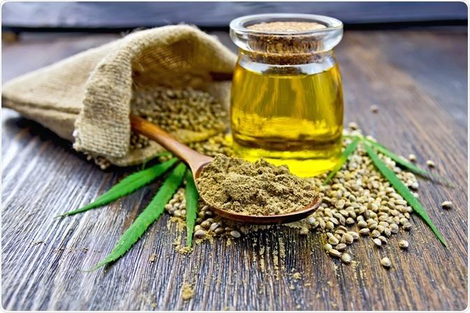 Harina del cáñamo en una cuchara al lado del aceite de cáñamo en el recipiente - foto tomada por el kostrez