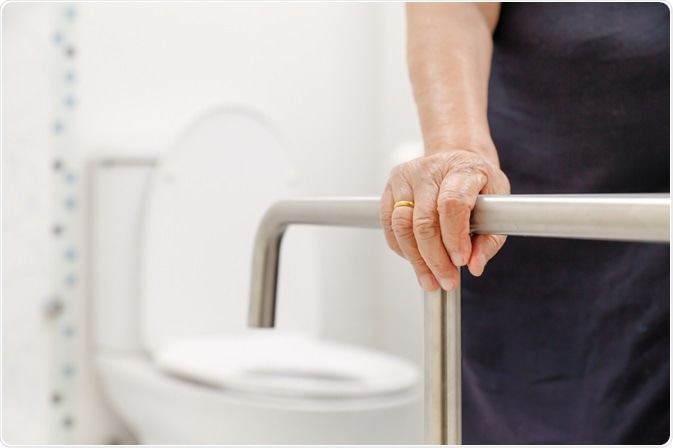 Elderly person holding old fashioned hand rail
