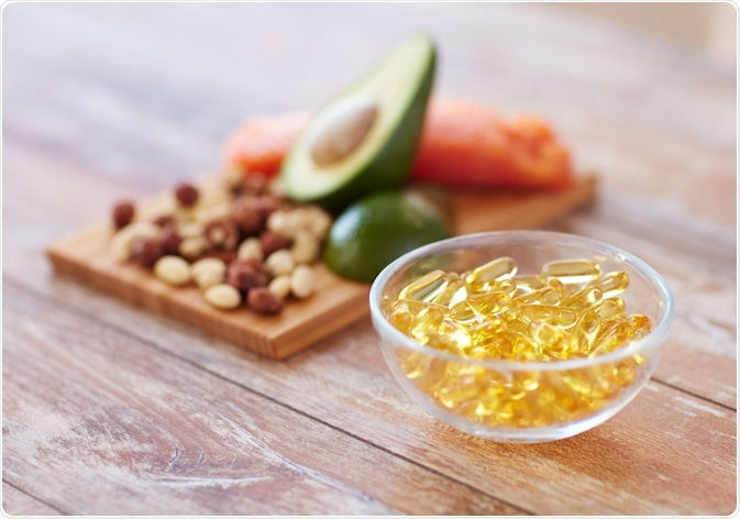 Photo of omega-3 supplements next to foods containing omega-3 - By Syda Productions