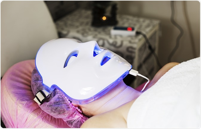 Photodynamic therapy facial mask on woman