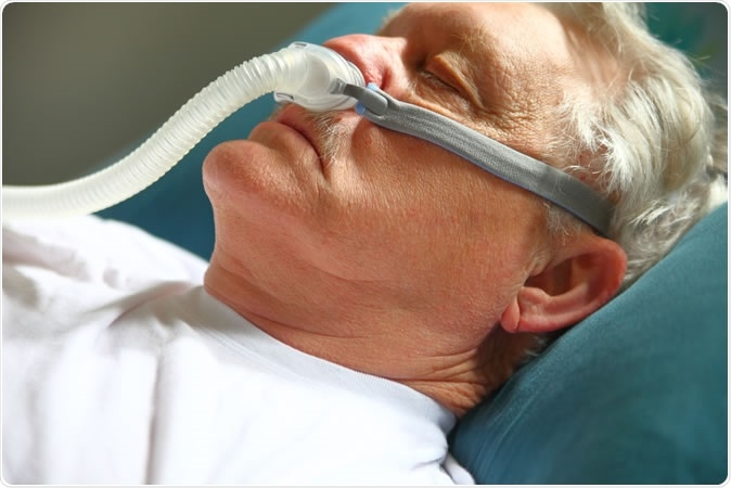 Male with breathing apparatus for sleep apnea.  Image Credit: Alice Day / Shutterstock