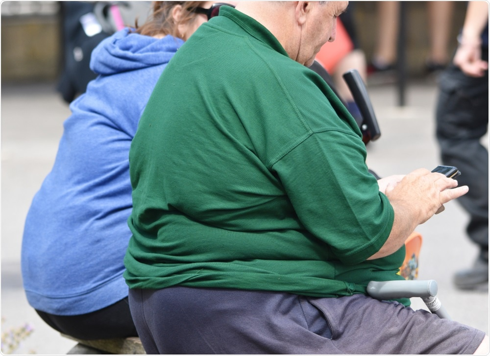 Obese adults sat on bench in town centre