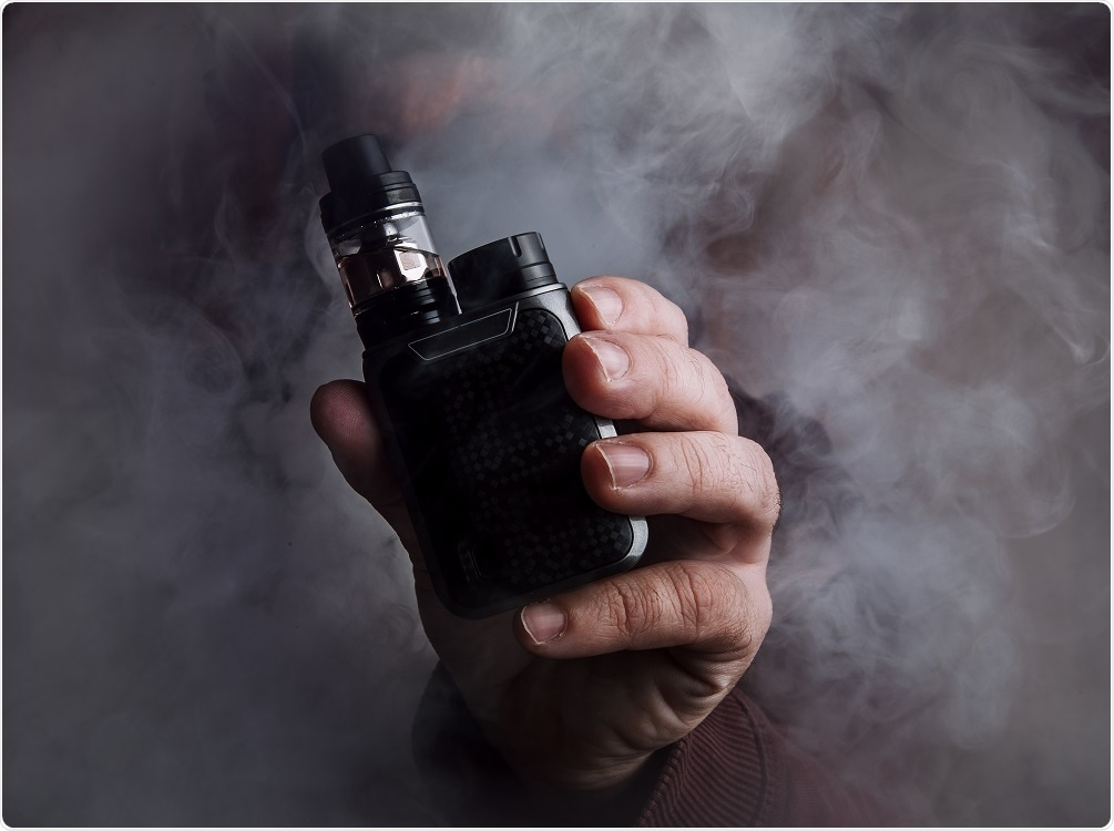 Person smoking e-cigarette with vapor in the air