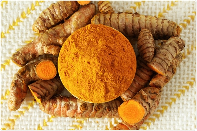 Turmeric or curcumin longa root powder and root. Image Credit: By Govindji / Shutterstock