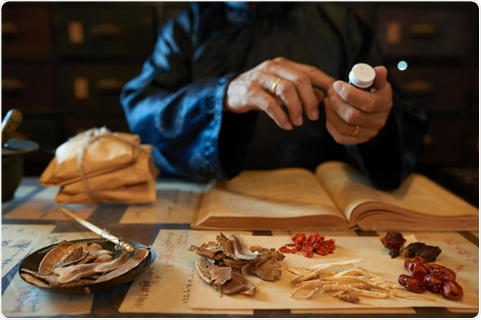 Practitioner making traditional Chinese remedy. Image Credit: Dragon Images / Shutterstock