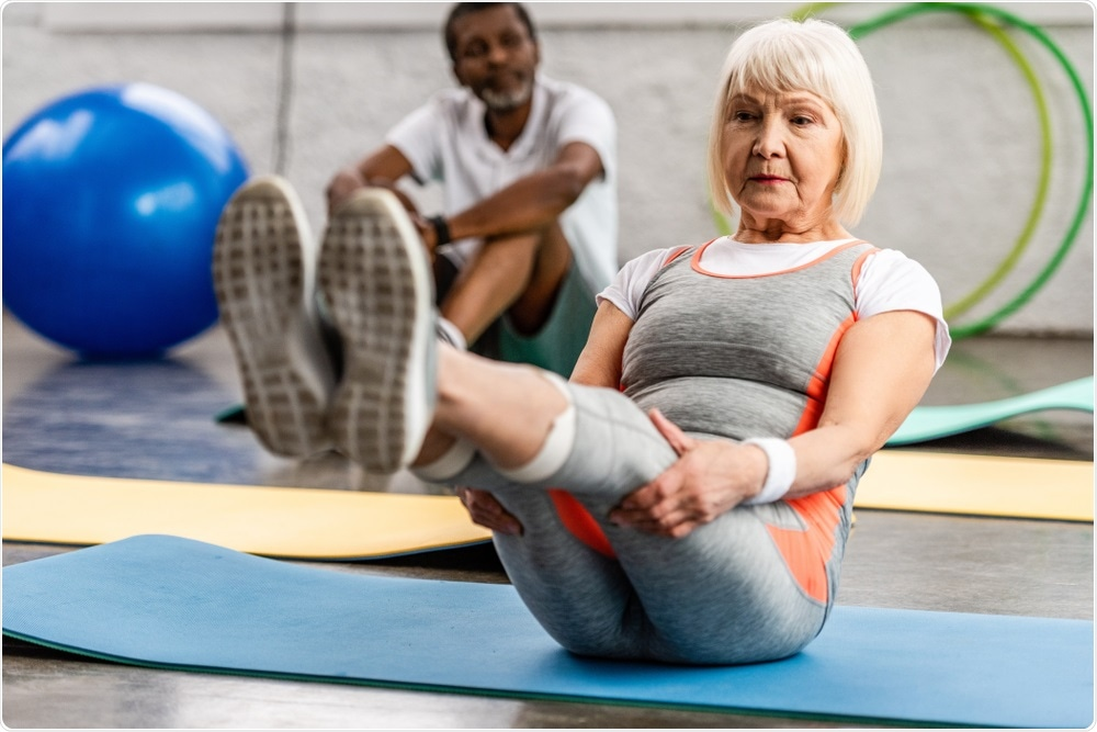 Older woman doing pilates, a form of exercise.