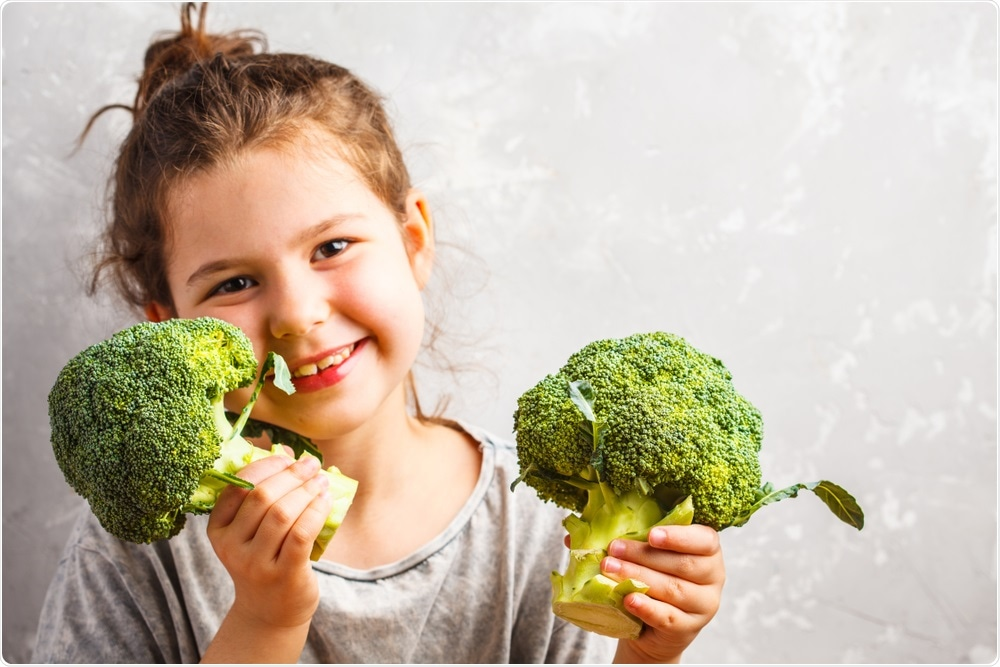 Child happy with broccoli in hands