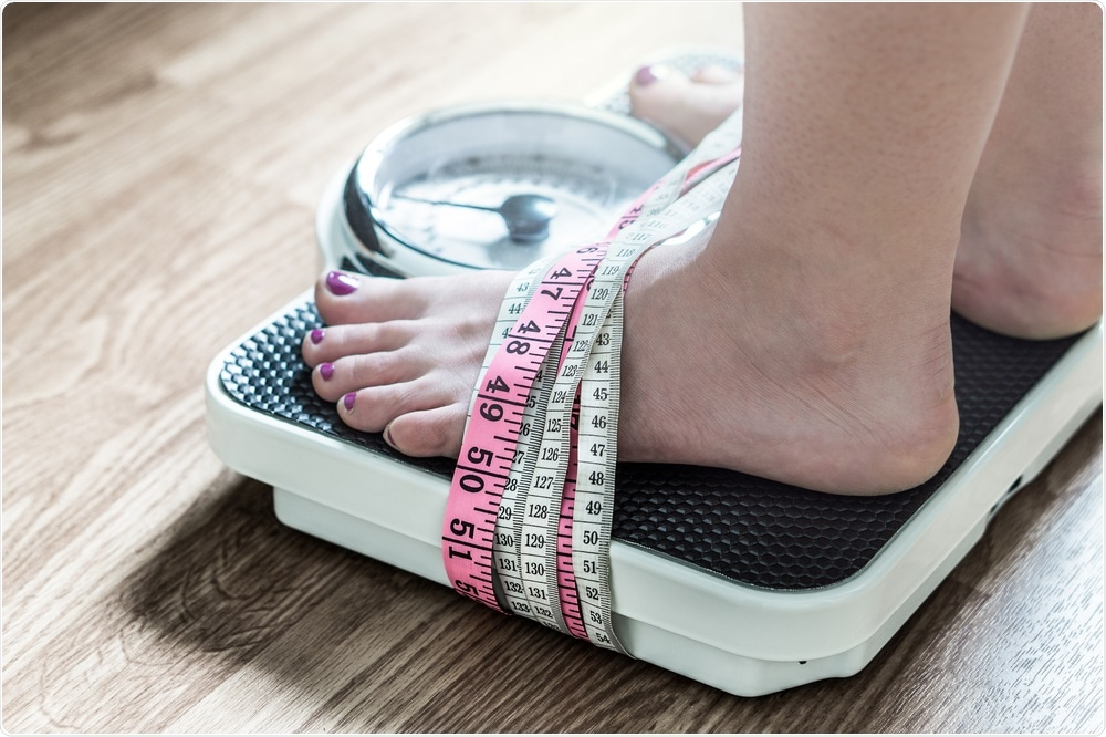 Woman stood on weighing scale.