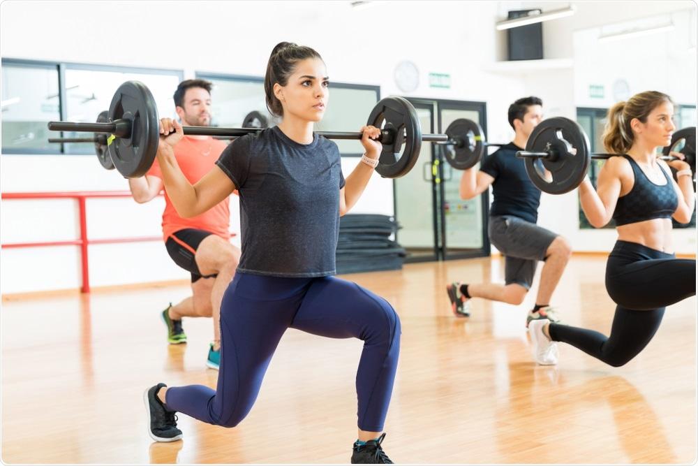 Mujer que hace levantamiento de pesas como parte de clase del ejercicio en el gimnasio local.