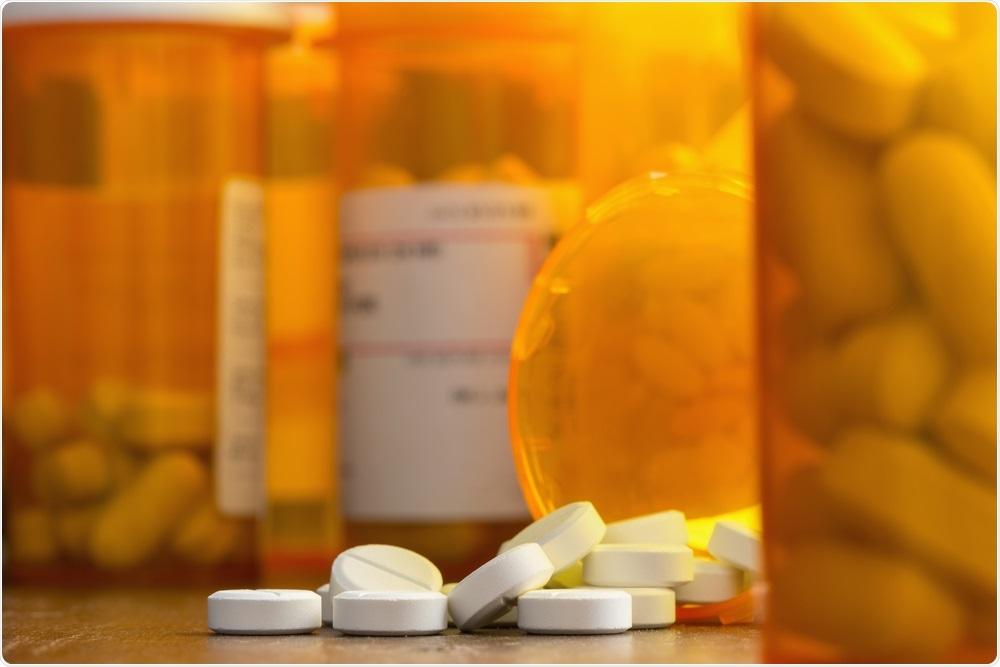 White opioid tablets in orange packaging