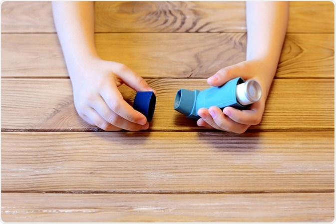 Child holding asthma inhaler in hands. Image Credit: OnlyZoia / Shutterstock