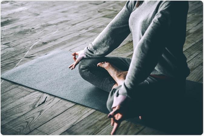 Young woman meditates while practicing yoga. Credit: Yulia Grigoryeva / Shutterstock