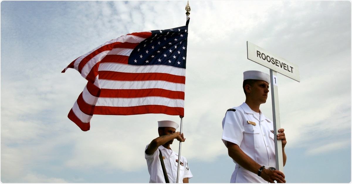 Study: An Outbreak of Covid-19 on an Aircraft Carrier. Image of American sailors with US flag - USS Theodore Roosevelt docked at the port of Taranto, Puglia, Italy. Image Credit: Massimo Todaro / Shutterstock