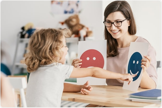 Emotion emoticons used by a psychologist during a therapy session with a child with an autism spectrum disorder. Image Credit: By Photographee.eu / Shutterstock