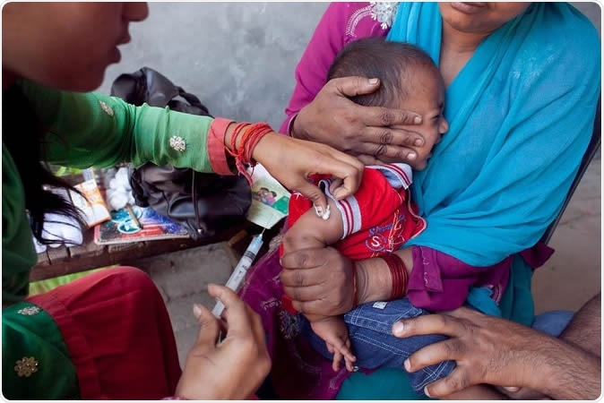 Moradabad, Uttar Pradesh, India. Measles shot administered to 11-month-old Armaan as his mother Fatima clutches him. Photo credit: UNICEF/India/Sumit Dayal