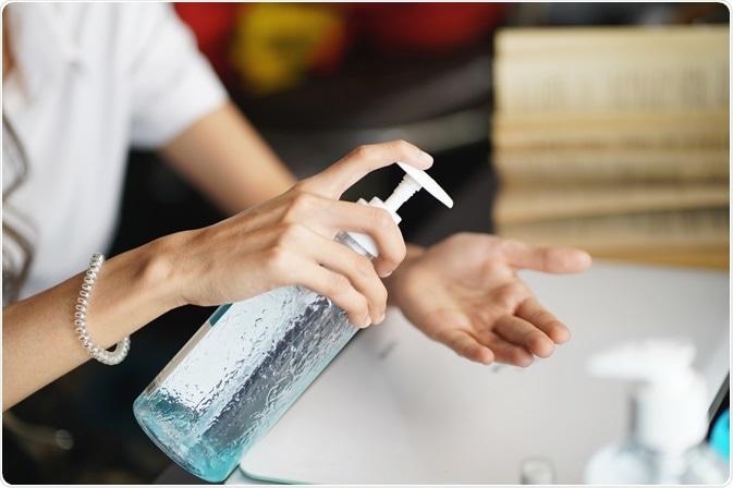 Donna che usando il prodotto disinfettante della mano