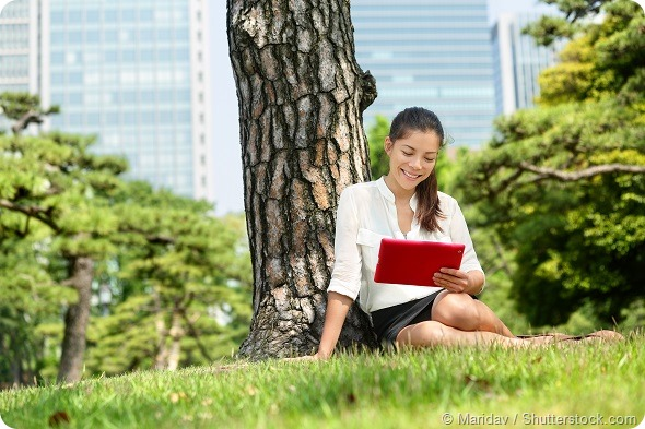 Asian business woman reading using tablet app in Tokyo