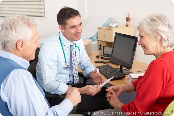 British GP talking to senior couple in surgery