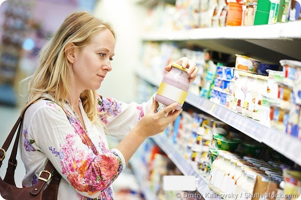 Young woman choosing fresh milk produces at shopping in dairy supermarket store