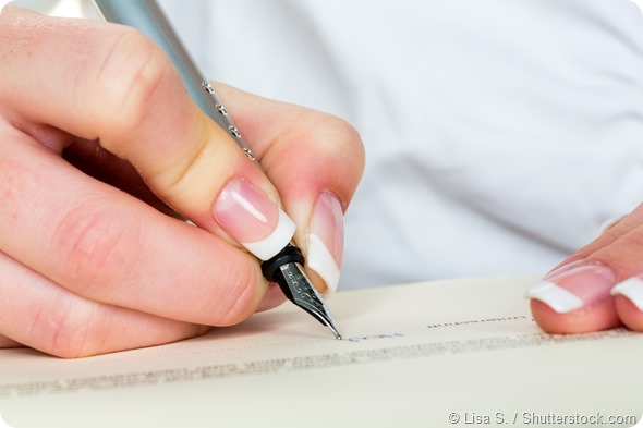 a woman signs a contract or a will with a fountain pen